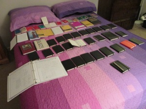 A number of notebooks of varying size and quality arrayed on a striped pink and purple bedspread.